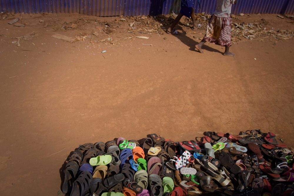 Children's bare feet walking by a pile of sandals