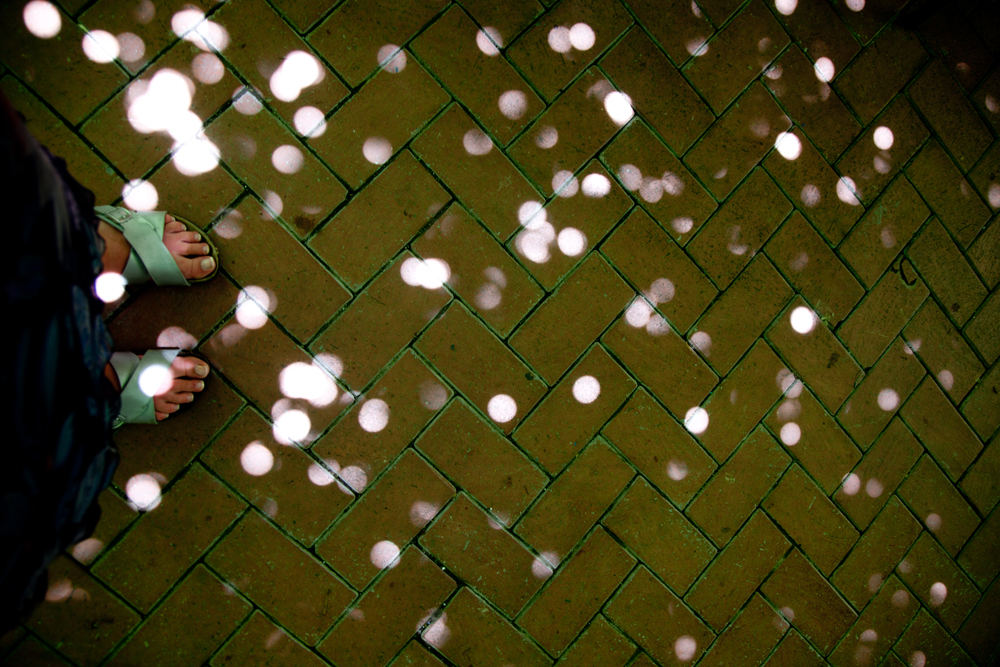 Spots of light falling onto someone's sandaled feet