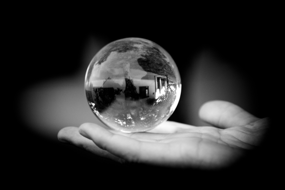 BW photo of a glass gazing ball in someone's hand