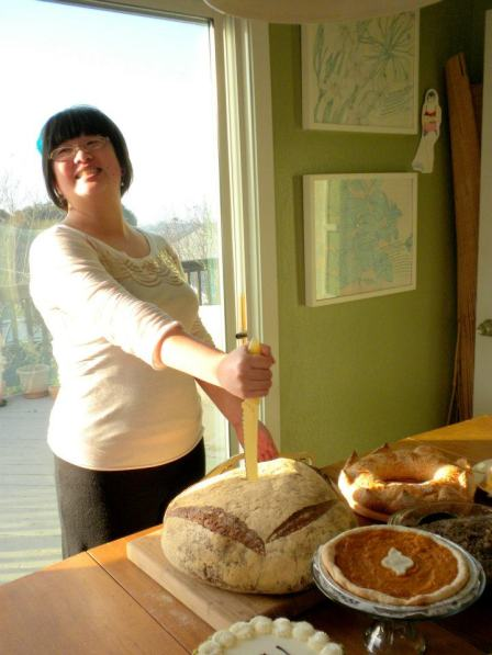 Lisa putting a bread knife into a giant loaf of bread
