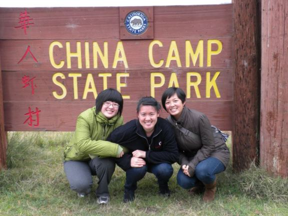 My with my two sisters in front of the sign for China Camp State Park