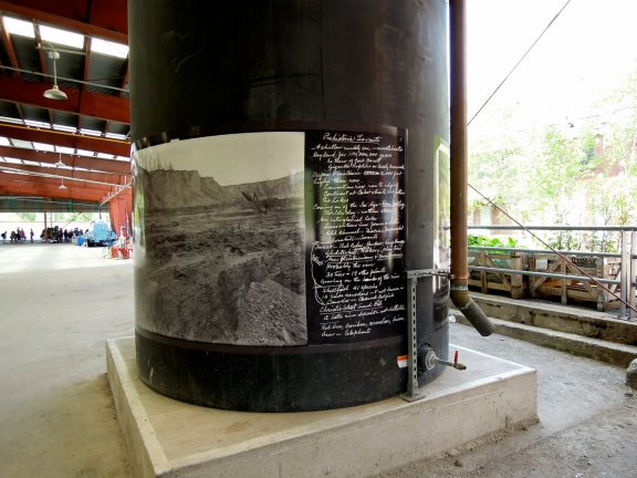 Banner-sized historical photos and notes posted onto a column/pipe from the original brickworks