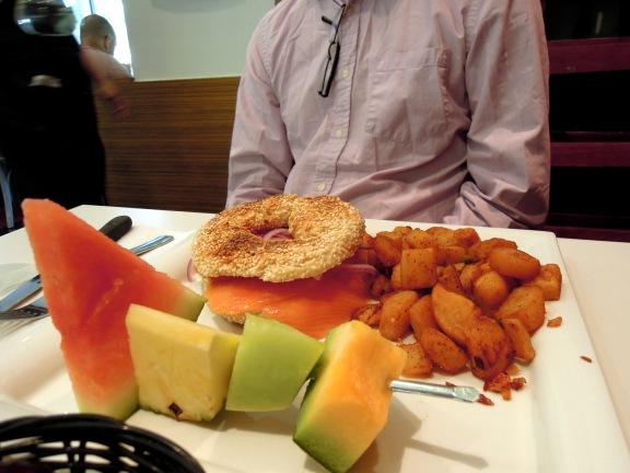 Erik's breakfast: fruit, smoked salmon and cream cheese on a bagel, potatoes.