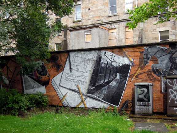 One part of a fabulous photorealistic mural depicting sketchbooks, pencils, and scenes from Glasgow