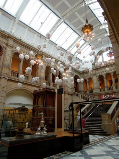 Hanging white mask sculptures in an exhibit hall