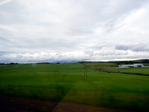 View from train back to Glasgow via different route: rolling grass
