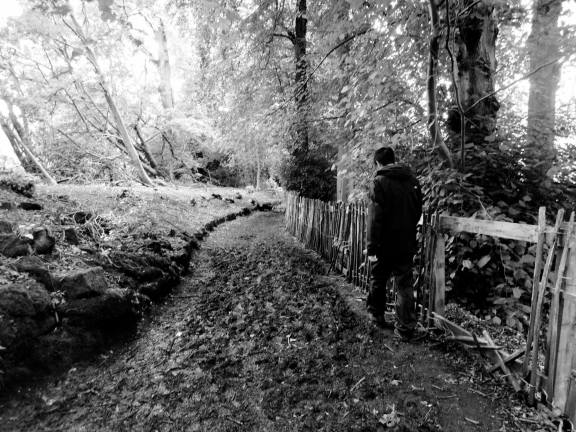 Erik picking his way across a muddy patch of trail (B/W)