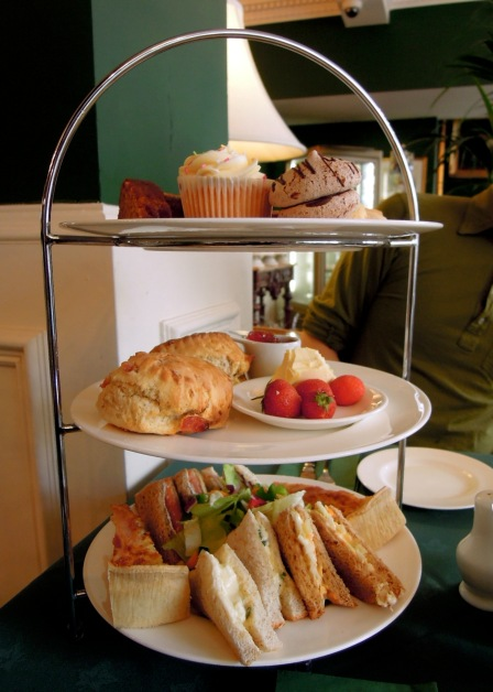 Three-tiered afternoon tea tray with cakes, scones, strawberries, sandwiches, and quiche.