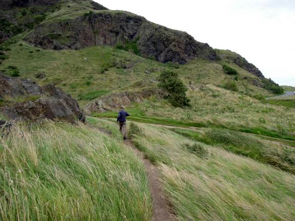 Trail at Holyrood Park with grasses blowing sideways in the wind