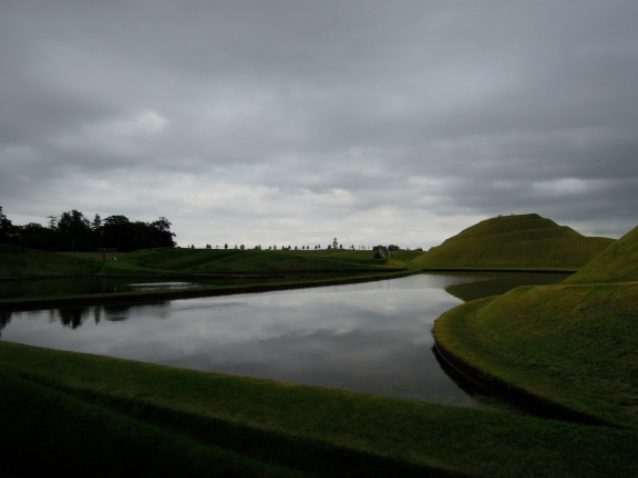 View of the Life Mounds and one of the pools of water, reflecting an overcast sky