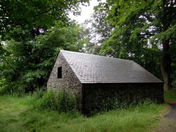 A cozy-looking, low-roofed stone house with a single square window in the short end
