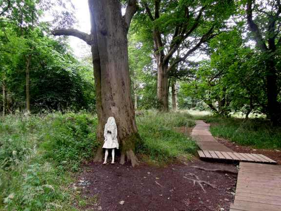 White statue of a weeping girl, leaning against a tree trunk