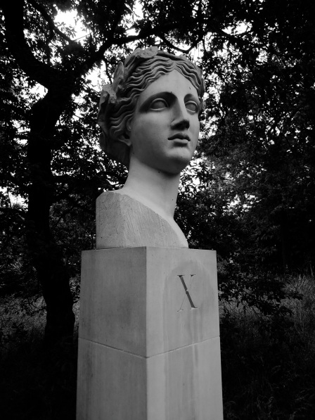 Head of Sappho on a pedestal with a serif X on it, in black and white.