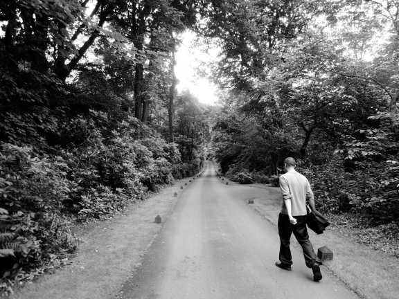 Erik leaving the park along the tree-lined path, in black and white