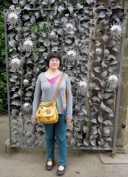 Lisa in front of the silver flowers and matte metal leaves of the entrance gates.