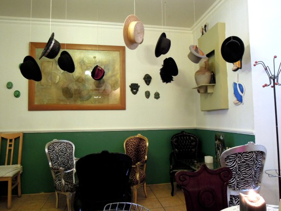 Back room of Qupi cafe, with vintage hats hanging from the ceiling, and mismatched chairs upholstered in leopard print