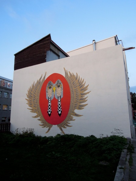 White wall decorated with a large painting of a stylized red phoenix