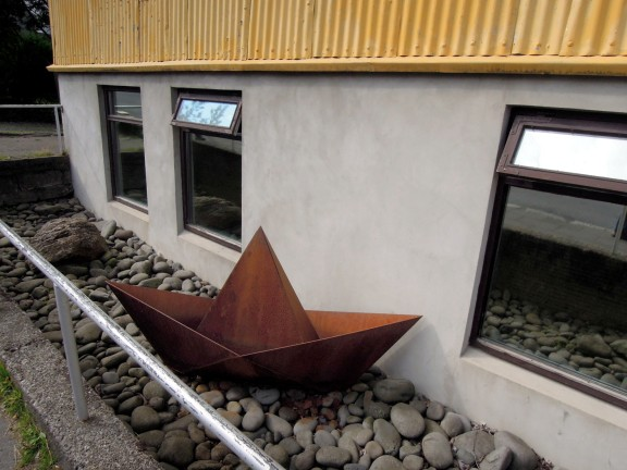 "Copper ""paper boat"" sculpture in a yard"