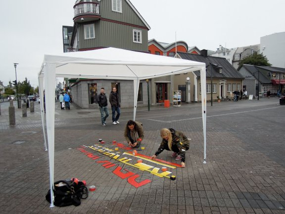 Two young people taping some lettering onto the ground