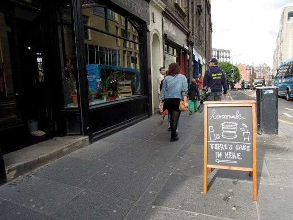 Sidewalk sign for Lovecrumbs Bakery in Edinburgh.