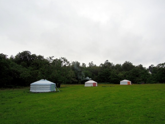 Three yurts in a field and the center one has smoke rising from the chimney pipe