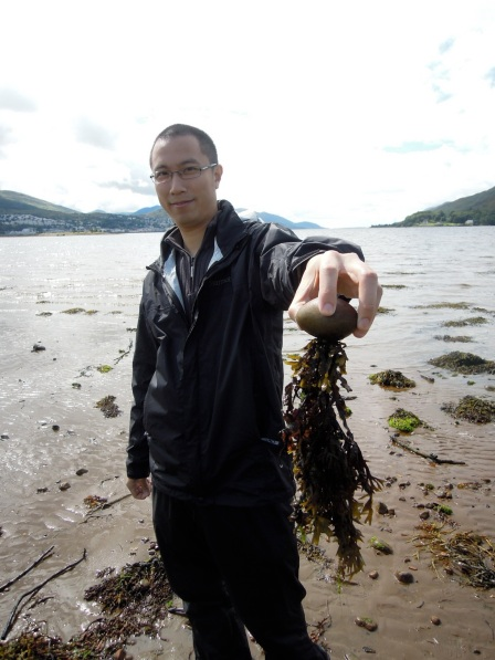 Erik holding a round rock with seaweed hanging down from it