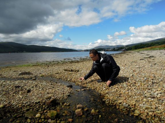 Erik squatting by a little stream on the beach at Caol waterfront