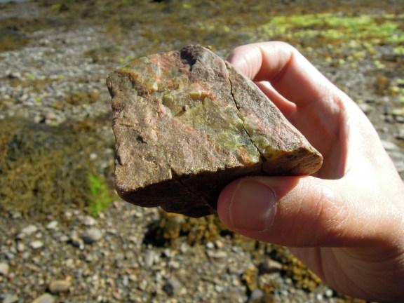 A multicolored rock held in Erik's hand