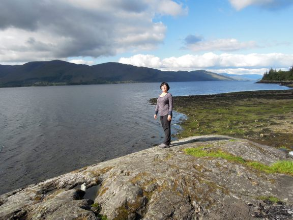 Lisa standing on a boulder next to Loch Linnhe