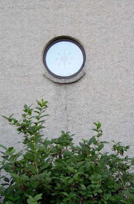 Round window with a snowflake design in the center