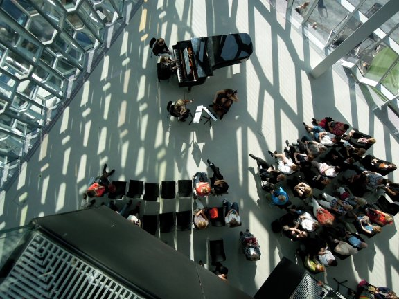 Young musicians performing in an atrium in Harpa concert hall, seen from above