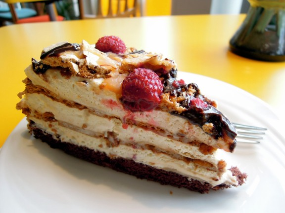 Meringue cake with chocolate and caramel syrup and raspberries
