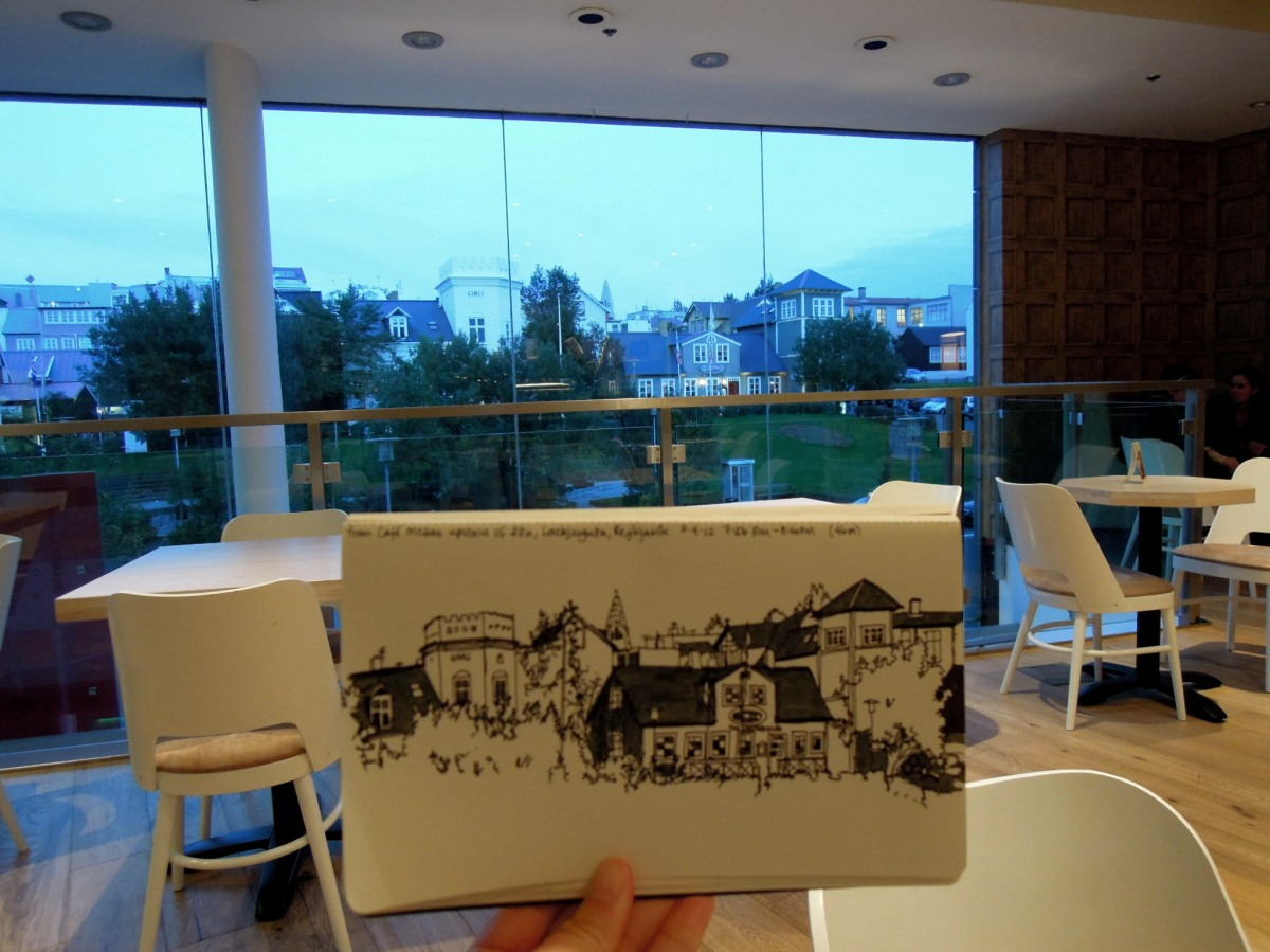 Holding up my sketch inside the cafe