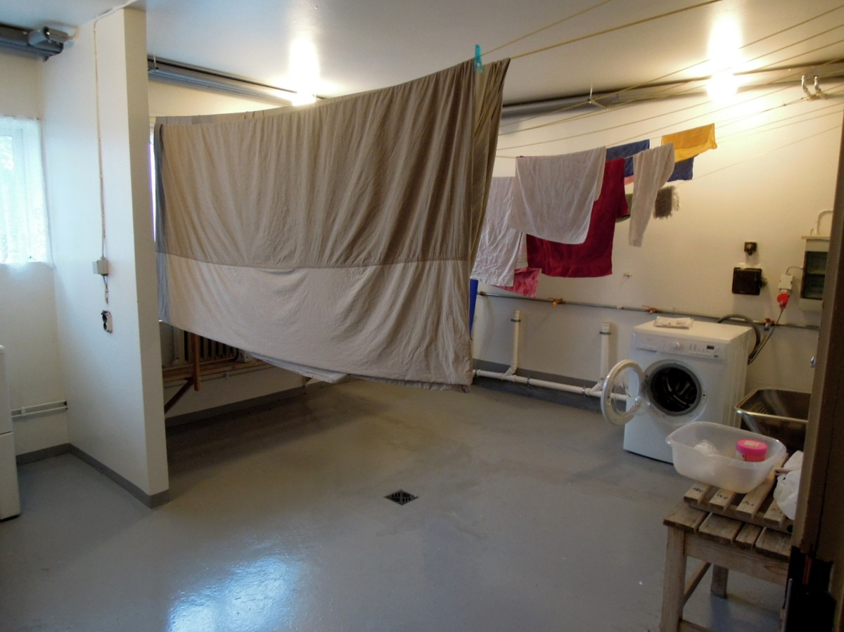 Laundry room with sheets hanging on the line