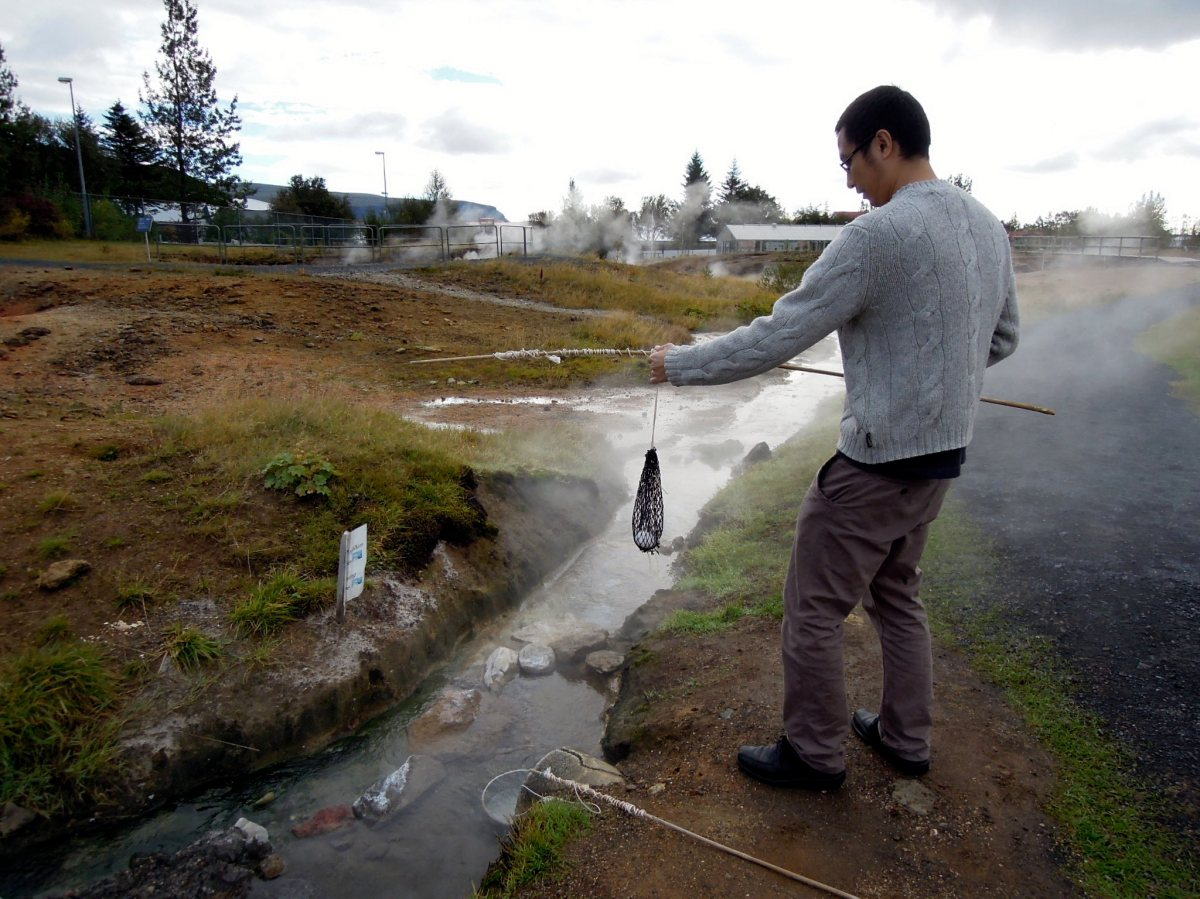 Erik dipping his egg into the hot spring, via a mesh net on a stick