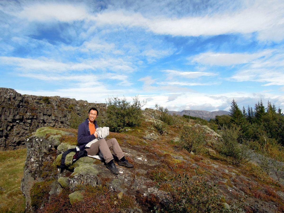 Erik sitting on a plant-covered boulder