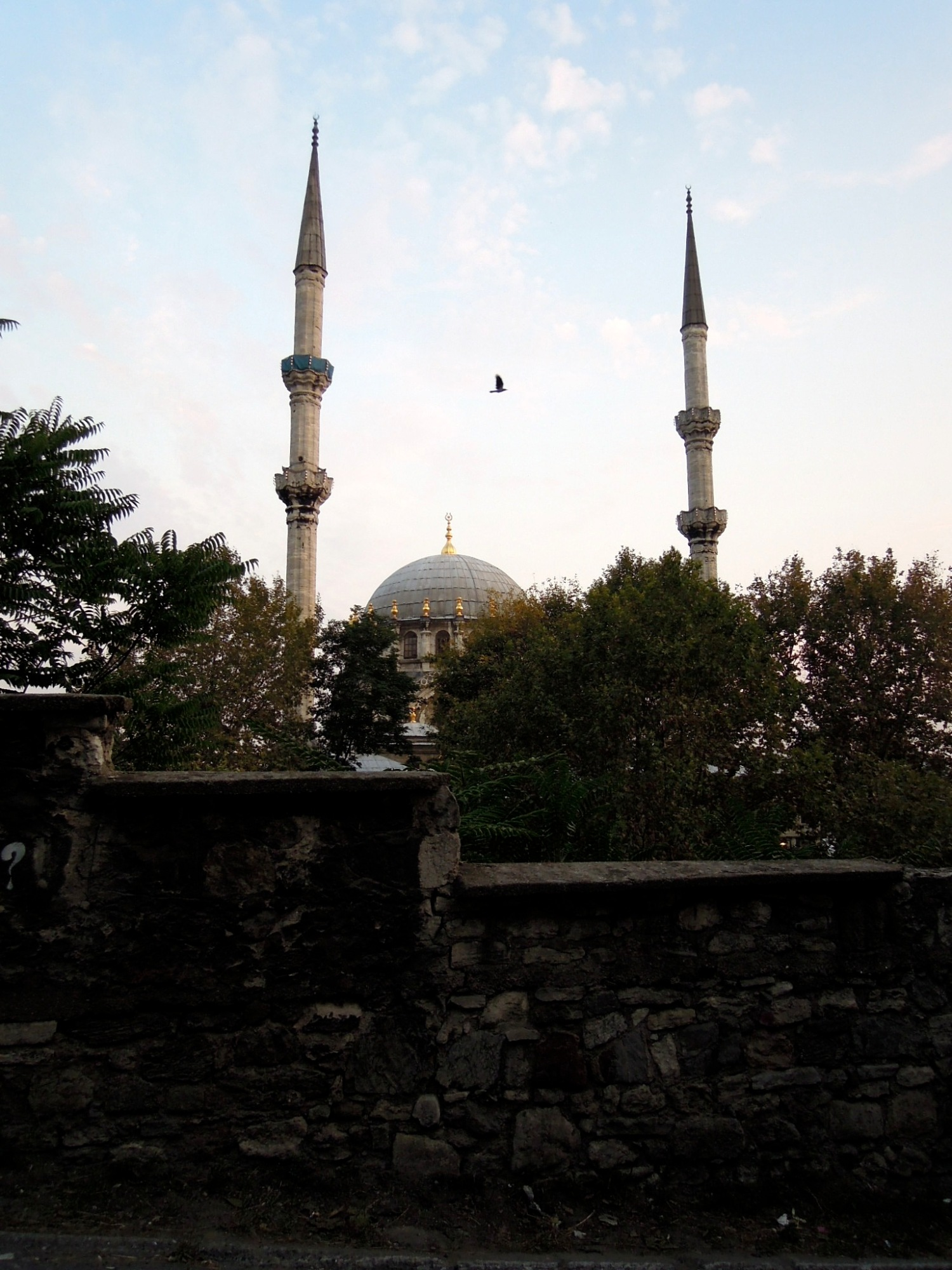 Mosque close to sundown with a bird flying overhead