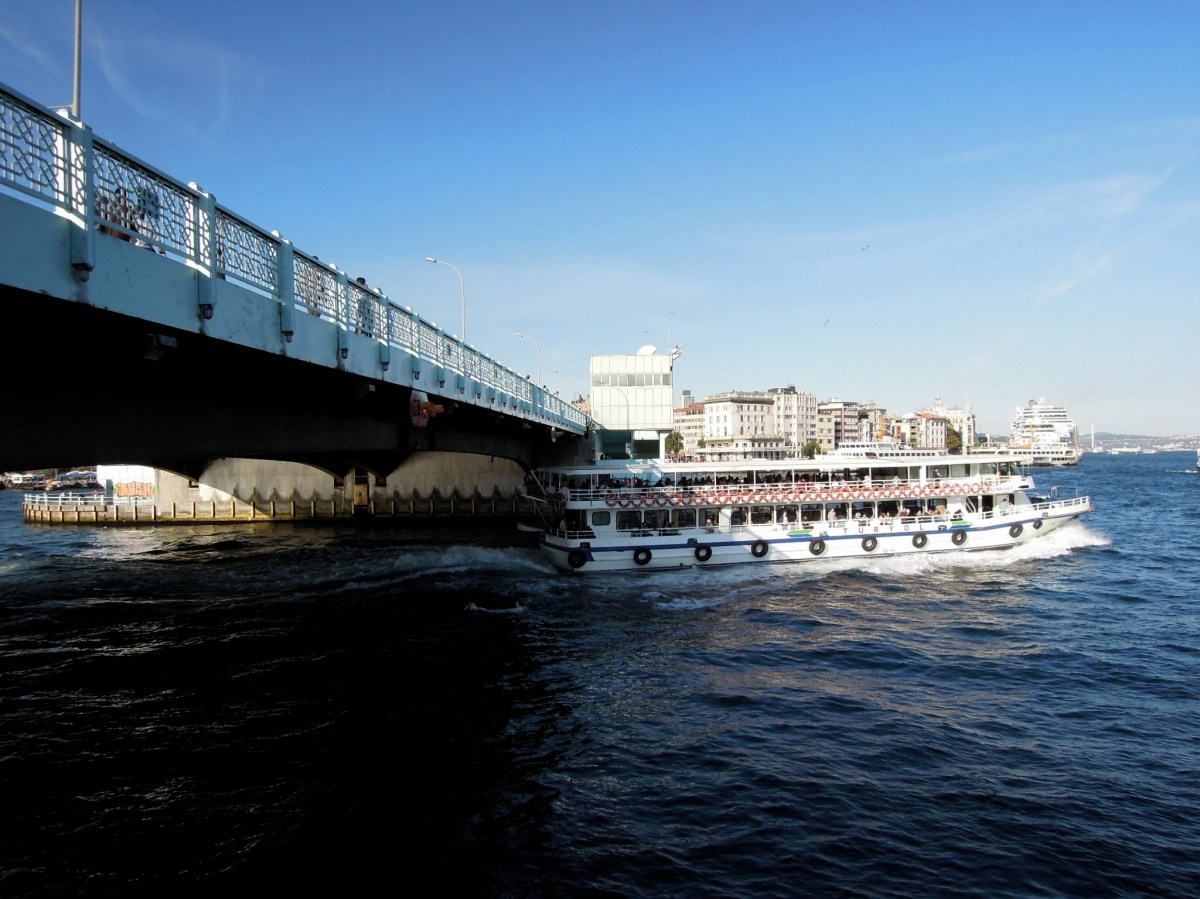 Boat passing under the Galata Bridge
