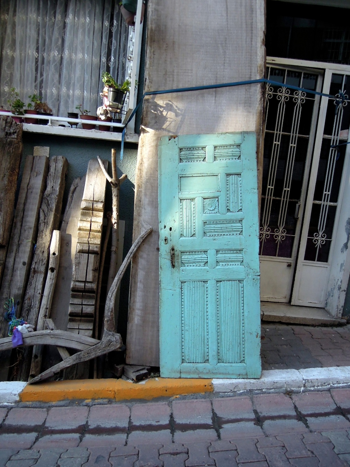 Carved turquoise door propped up against a building wall