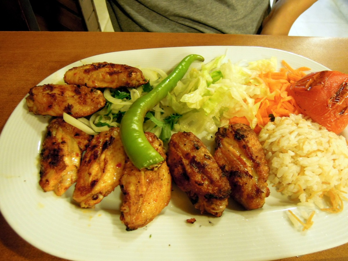 Chicken wings with rice, shredded carrots and lettuce and onions