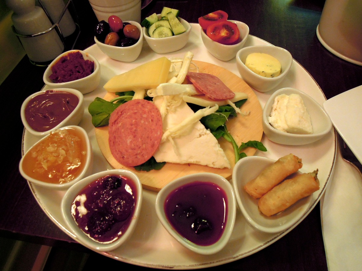 Yımırta breakfast plate with cheeses, salami, arugula (rocket), cucumbers, tomatoes, olives, and spreads