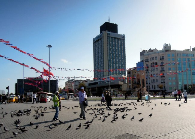 People, pigeons, and bunting on Taksim Square