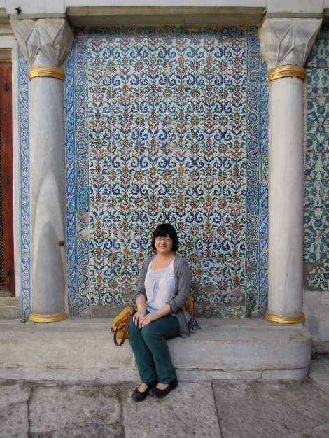 Lisa sitting against a tiled wall in the Queen Mother's Courtyard