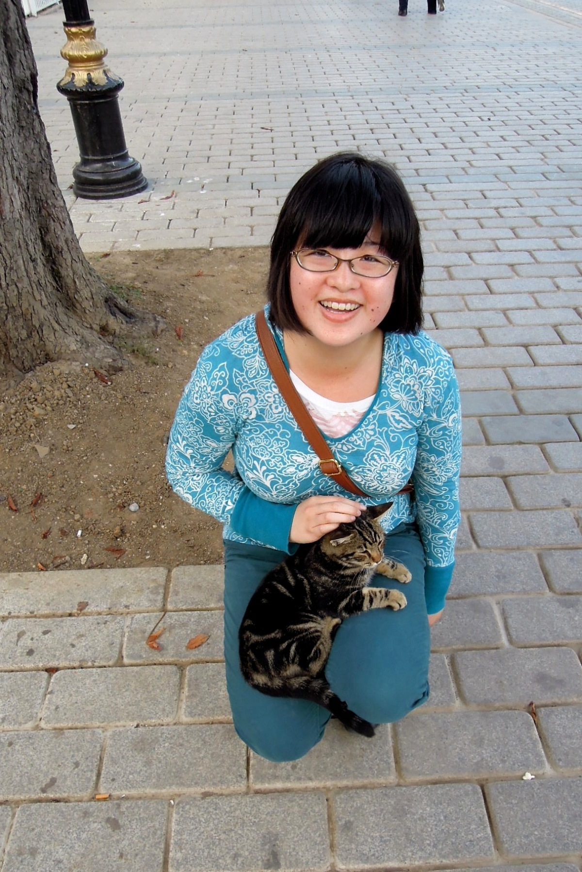 Very happy Lisa squatting on the ground with a little tabby kitten on her lap