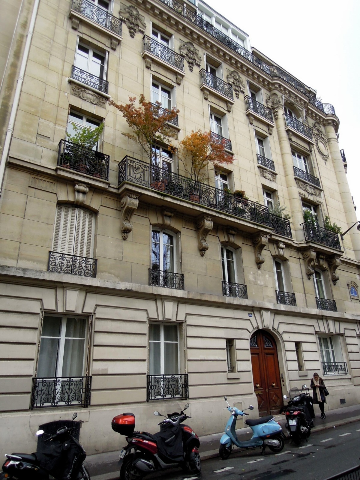 Parisian apartment building with potted trees on the balcony