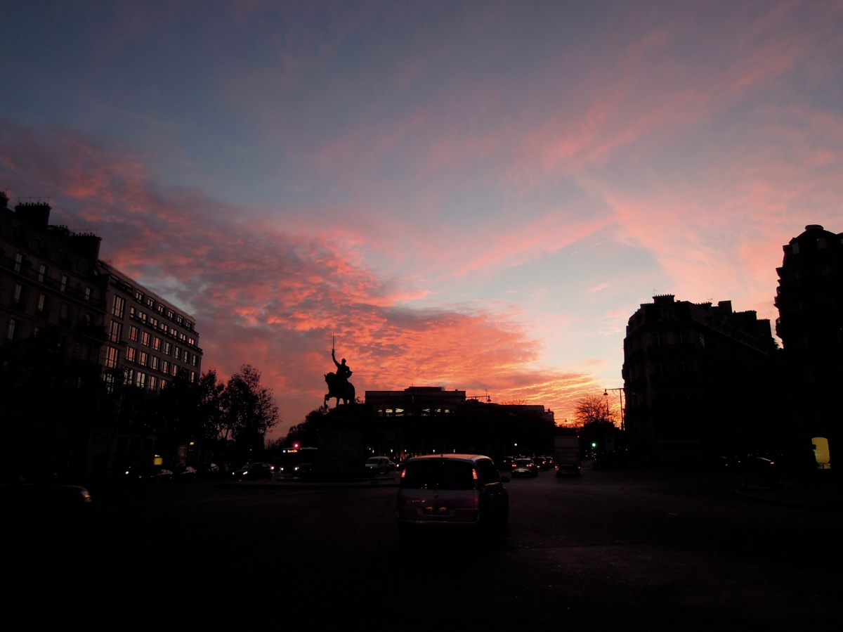Statue of an equestrian George Washington, silhouetted against a pinky-red sunset