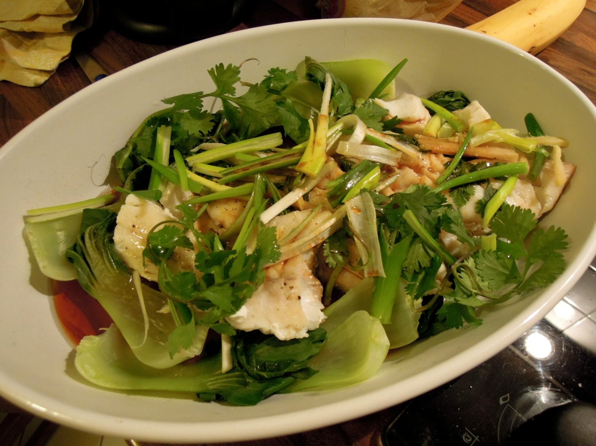 Chinese-style steamed fish and bok choy with ginger, green onions, and cilantro