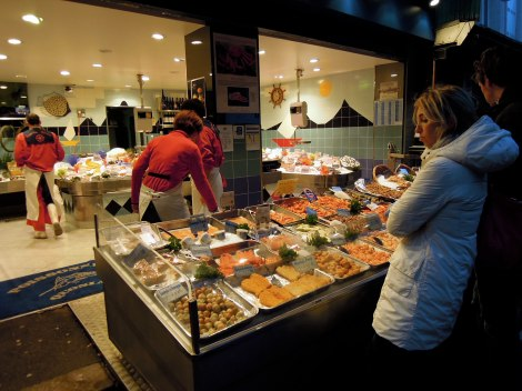 Outside display at a poissonnerie, at night, with customers looking at the fish