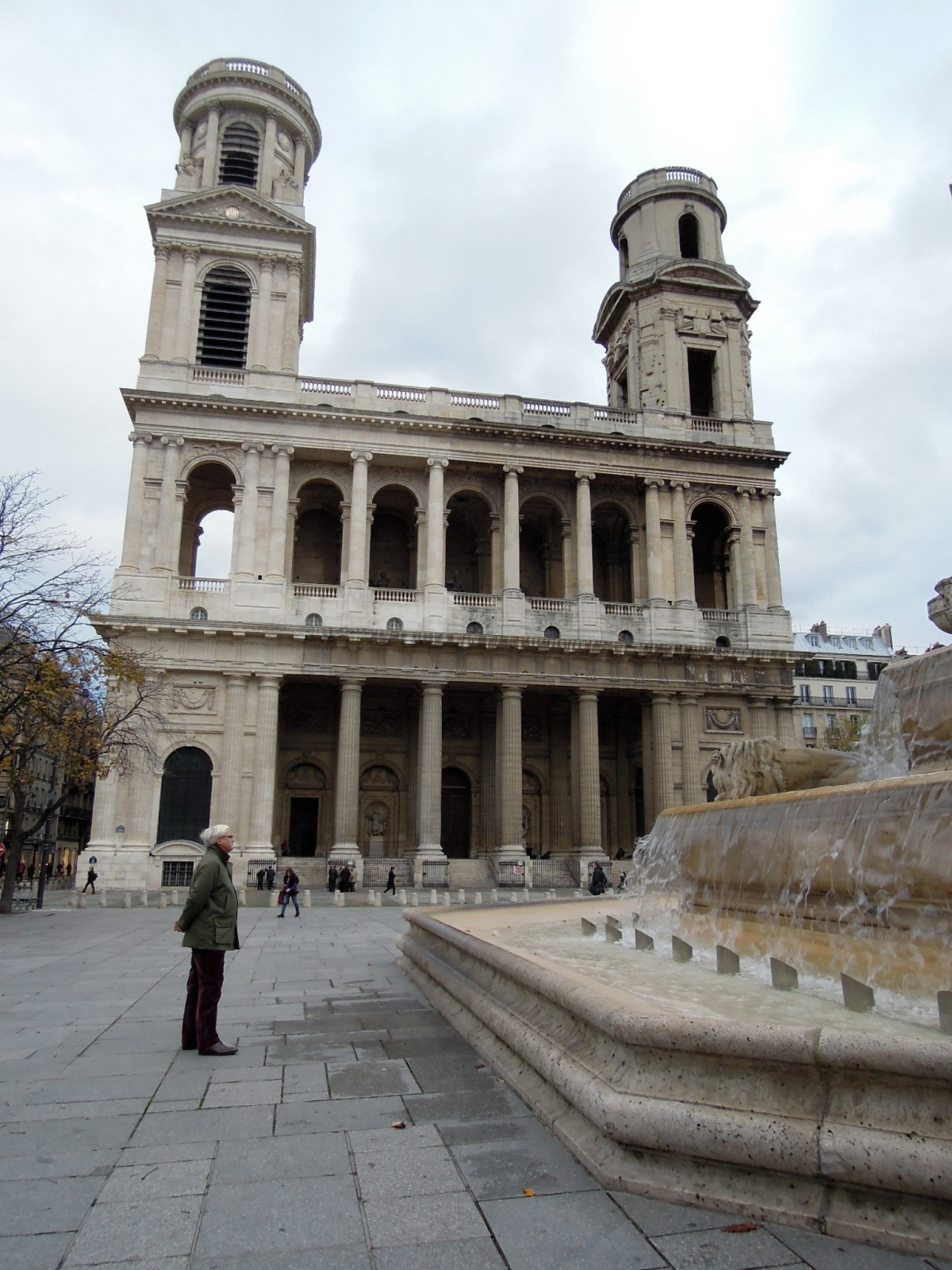 Man looking at the fountain outside Saint-Sulpice