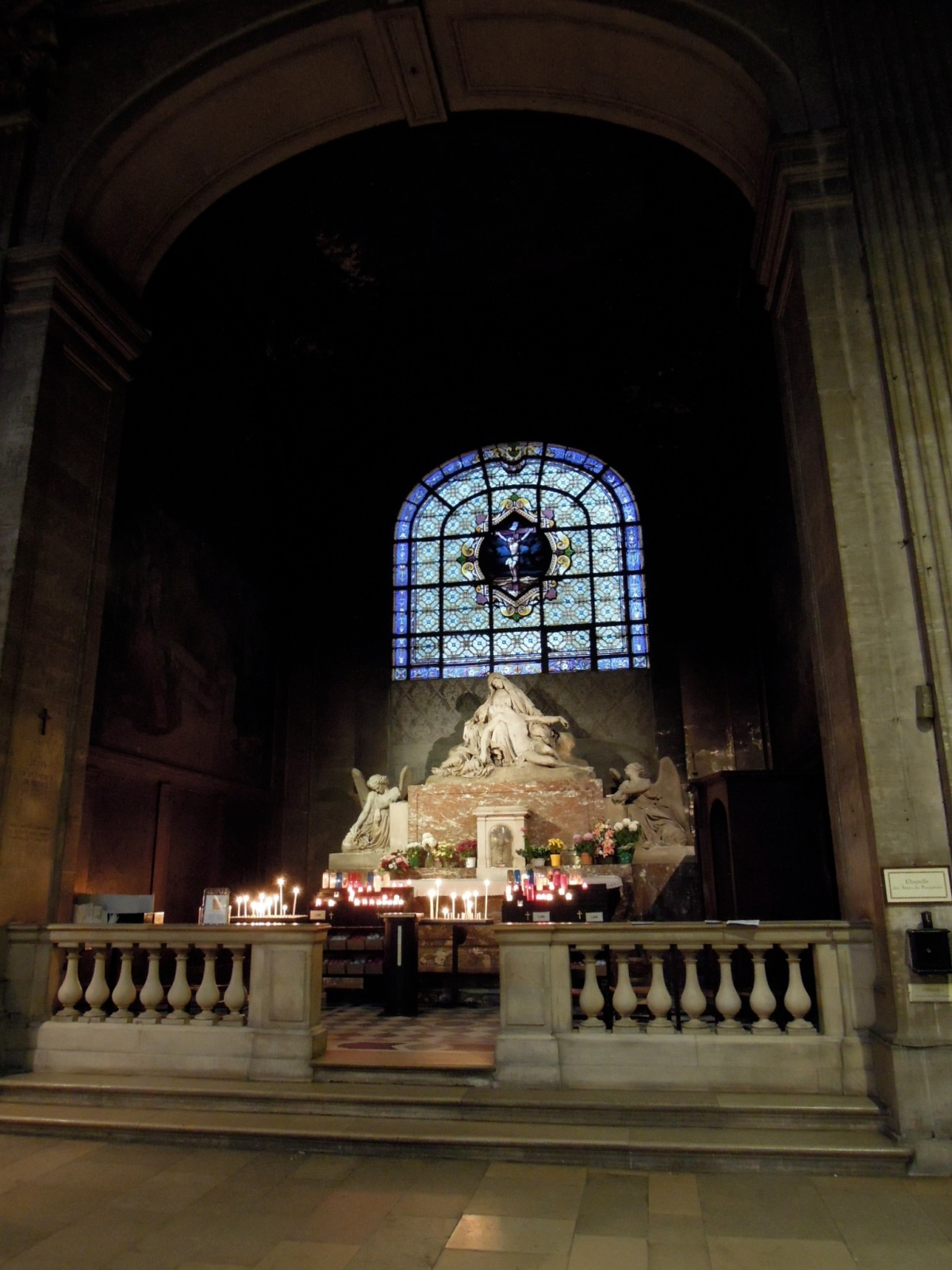 A chapel with candles inside Saint-Sulpice